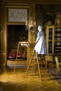 Early-20th century - Housemaid cleaning chandelier in Sweden.