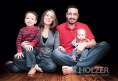 Family photo black background indoors hardwood floor