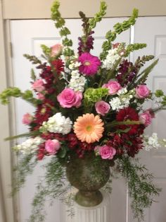Fresh Church Arrangement using mixed colored gerbera daisies, pink roses, burgundy snapdragons, white stock, bells of Ireland, red Astros, mixed greenery. (First Baptist-Booneville, MS). January 17, 2016
