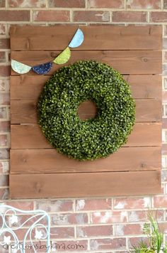 Boxwood Wreath for the Front Porch. Hanging it on a wooden sign for more impact.