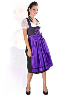 Fairytale violet dirndl. The black satin dress is softly tailored to flatter your curves and it stops just below the knee. No fairytale heroine is complete without a pretty bodice and this one is embellished with violet embroidery and classic corsetry detailing. The white under blouse has a low cut sweetheart neckline and delightful see through sleeves in delicate white lace. Finally, the outfit is topped off by a violet a violet apron featuring black polka dots and a bow.