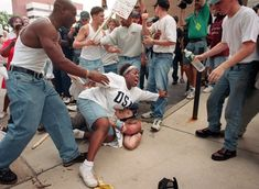 June 22, 1996 – Then 18-year-old Keshia Thomas of Ann Arbor shields a man wearing a Confederate T-shirt from an angry crowd during a Ku Klux Klan rally outside Ann Arbor's city hall. (I love this woman)