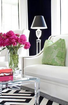 White sofa.  Lucite lamp & coffee table.  Graphic black & white rug. Black walls.
