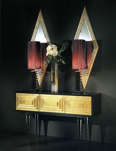 """""""Gallery"""" and couture console. Part of a couture collection of highly stylised design ethos and essence. Shown here in black ebony contrasting with gold leaf. The architectural profile of the body is emphasised by the highly decorative and crisp raised geometric design; this is in contrast to the extremely exaggerated sculptural tapered legs, defined by the lentil motif on the knee of the leg. Emphasis on traditional cabinet making and production."""