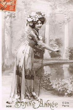 円柱の並ぶ庭園の池のほとりで、美しいドレスに身を包んだ貴婦人の姿が描かれたポストカード。モノクロの写真にほのかな色付けが施された幻想的な雰囲気です。エヴァへ新年のあいさつを兼ねたノエルのカードです。フ…