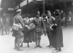 Women police patrols giving information to men on leave at a London railway terminus, WW1
