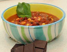 Für das Chili con Carne mit dunkler Schokolade das Fleisch in kleine Würfel schneiden. Öl in einem Topf erhitzen, Fleischwürfel, Zwiebeln und
