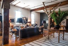 That couch. Those leather camp stools. The scored wooden columns. The white striped rug. Scott & Kristan's Inspiring Arts District Loft