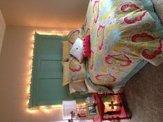 DIY ROOM! Headboard made from old door with crown molding added (bottom part is bead-board framed), Red table was stripped and repainted, and added some lights for a little festivity!