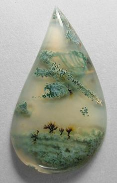 Moss agate - This is so cool! I see a little landscape scene with trees and some neat clouds.