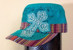 This turquoise cadet cap features a dark turquoise screen printed Aztec pattern across the front of the hat. The bill is covered in a multicolored striped fabric and there is a matching one inch band of fabric that lines the bottom of the cap. A turquoise piece of fabric, embellished with dark green embroidery thread, covers part of the bill and is distressed/torn for a fun 'worn' look. The hat also features a turquoise fabric cross embellished with silver rhinestones and silver thread.