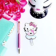Cute Hello Kitty planner paperclip paparazzi.  This adorable Hello Kitty is taking pictures with her Hello Kitty instax.  Add cuteness overload to your planner pockets!