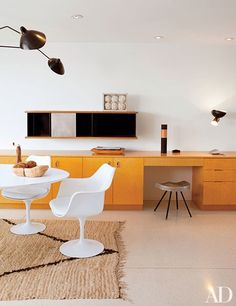 The kitchen of the Richard Neutra–designed Singleton House features an Eero Saarinen Tulip table and chairs by Knoll and built-in cabinets by Neutra   archdigest.com
