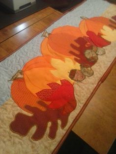 Fall/ Autumn pumpkin with red yellow and brown leaves. Acorns as well, table runner