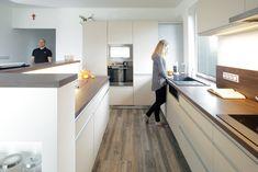 Barva dvířek bílá káva nebo slonová kost působí jemně s bílou omítkou. Žádaný kontrast pracovní desky v tmavém dřevodekoru umožní propojit kuchyň s obývacím pokojem, kde se tmavé dřevo bude používat na nábytku.