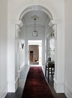 A grand, white foyer with hanging light fixture, red rug, and crown molding