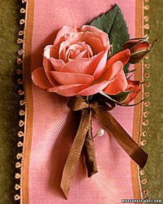 A perfect-shaped rose makes a handsome boutonniere when wrapped with its own buds in brown silk ribbon.