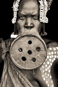 Among the Surma (own name Suri) & Mursi people of the lower Omo River valley in Ethiopia, about 6 to 12 months before marriage the lip is pierced by her mother or kinswomen, usually at around the age of 15 to 18. The initial piercing is done & a wooden peg inserted. After the wound has healed, the peg is replaced with a slightly bigger one. Plate inserted at 4cm, final plate dia. about  8cm to over 20cm. Women craft own plates with pride.