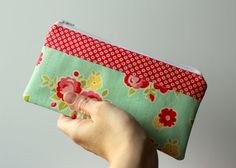 These little bags are so versatile. They are the perfect size to hold pens and pencils, snacks, hygiene products, make up, toys, coupons, money, etc. This bag was made with Riley Blake Aqua Floral and Red Starburst from the Sidewalks collection. #rileyblakedesigns #sidewalks #vintagemodern #pouch