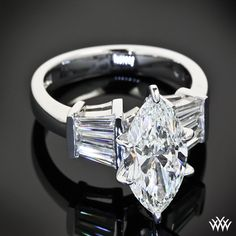 This unique Diamond Engagement Ring is set in 18k white gold and holds 6 Baguette cut diamonds (0.85ctw). The 6 prong head holds a 2.55ct Marquise Cut Diamond.
