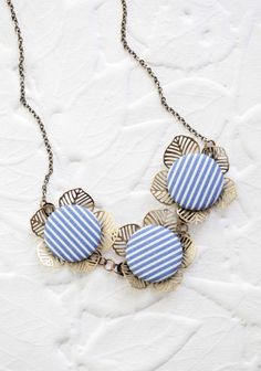"Genuine Delight Floral Indie Necklace 39.99 at shopruche.com. Striped blue and white buttons lend the perfect hint of nautical charm to this whimsical brass necklace with a trio of cheerful blooms.13"" long"