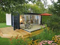 """The Ecopod. """"Made from a shipping container, an electric winch is used to raise and lower the heavy deck door (power is supplied by a solar panel). The floor is made from recycled car tires, and the walls have birch paneling (over closed-cell soya foam insulation). The glass is double paned to slow heat transfer."""""""