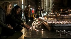 Des badeaux allument des bougies en hommage aux victimes des attentats de Paris, samedi 14 novembre 2015 à Lyon (Rhône). | JEFF PACHOUD / AFP