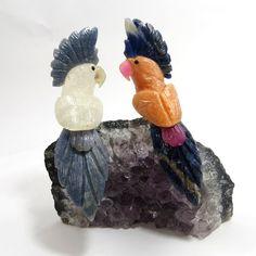 Pássaro - Cacatua - ID:3991. Esculpidos artesanalmente em Cristal de Quartzo e Calcita Laranja, com detalhes em Quartzo Azul, Sodalita e Ágatas, na base de Ametista em formação Natural.