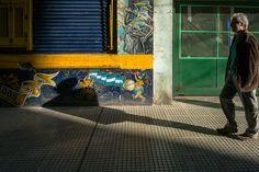 """Licht und Schatten im Stadtteil La Boca von Buenos Aires, Argentinien. Das Foto wurde gegenüber der Bombonera, dem Stadion der Boca Juniors, gemacht. Mit seinen vielen bunten Grafittis und bröckelnden Fasseden ist das traditionelle Viertel """"La Boca"""" reich an Motiven für Street Photography."""