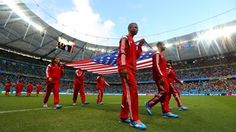 Flag bearers walk in the pitch with the national flag of the United States