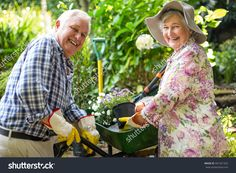Portrait of happy senior couple with potted plants in garden