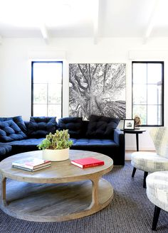 White walls, black and white wall art, blue couch, wooden coffee table, striped chairs, and grey rug