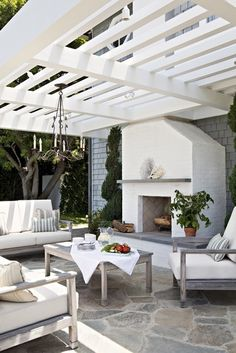 """Tim Barber, of Tim Barber Ltd. """"In Southern California, we look for opportunities for outdoor living everywhere. A brick fireplace, a white-painted pergola and a bluestone terrace added to an unused spot behind the home to create the perfect destination for afternoon lemonade or cocktails at sunset. The wet-rated chandelier, easy-care teak furniture and performance fabrics make this outdoor space strictly low-maintenance."""""""