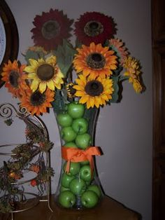 I like the artificial green apples in the tall container. Great floral idea for home decor.