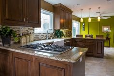 The open plan of this traditional kitchen connects the room to the dining area as well as the views to the exterior and makes it one large, family-friendly space. The bright accent wall in Gecko green by Dunn Edwards adds a fantastically fresh pop of color!