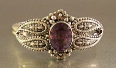This vintage Victorian Revival sterling amethyst cuff bracelet is fairly ornate, with a raised floral design. It is marked RD and STERLING,