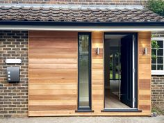 Modern and timeless cedar clad front porch Wooden Cladding, Cedar Cladding, House Cladding, Exterior Cladding, Facade House, Porch Sliding Doors, Front Doors, Garage Doors, Modern Bungalow Exterior