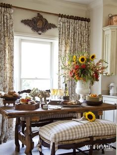 Charming country feel dining room with a farmhouse table and pretty neutral plaid benches.