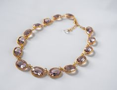 My classic, signature crown settings are now available with offset loops! The loops at the top of the setting prevent the stones from flipping over. This necklace will always hang perfectly and is great for layering! The stones in this exquisite necklace are genuine vintage Swarovski in a beautiful, versatile Light Amethyst! Stone Size: 18x13mm / .70 inches / 1.8cm each Stone Material: Vintage Swarovski clear stones in Light Amethyst Settings: Heavy cast Brass with your choice of p...