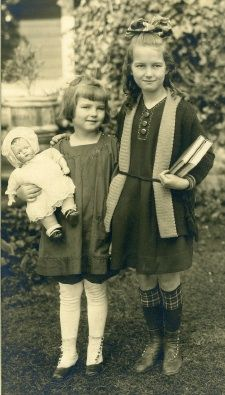 Antique photo of sisters, one holding her doll, circa early 1900's.