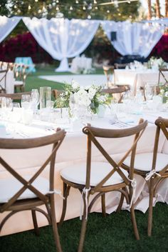 Arrangements Floral + Party Design — Rancho Mirage, Lauren + Chris | Outdoor reception dining setting, wooden cross-back chairs, white and green floral arrangement,s, canopy with sheer draping, outdoor string lighting