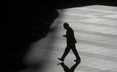 Image: A man looks at his cell phone as he walks into the shadows. YOU'RE EVERY MOVE IS BEING WATCHED