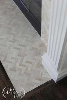 Tile with soft tones, pattern interest in the fire place surround shows off the white trim and contrasts against dark wood flooring.