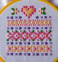 Cross-stitch heart and patterns in pink, yellow and purple on white aida