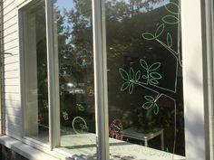 Een DIY raamversiering van de herfst (waaiende herfstblaadjes, boom, paddenstoelen, egel en blazende wolk).Deze krijtstift tekening zet je zelf op het raam.