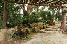 Aquascape Inc.      A pergola made from trees creates an intimate feeling for this Pondless Waterfall.