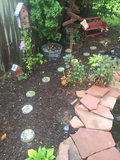 Various Pinterest projects in our whimsy corner: Stepping stones, birdhouses, fairy garden, pot toadstools and sign post. I love this little corner of our back yard!