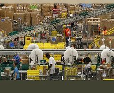 "Amazon Fulfillment center employees process inbound goods to add to the warehouse inventory during ""Cyber Monday.""A number of seasonal emplo..."