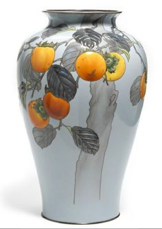 A moriage cloisonné enamel vase By the workshop of Ando Jubei, early 20th century. The slender ovoid body worked in silver wire and brightly colored enamels with a persimmon tree with leafy branches heavy with the orange-hued fruit silhouetted against a pale blue ground, with silver rim bands. Sold at Bonhams 2012 for $60,000.