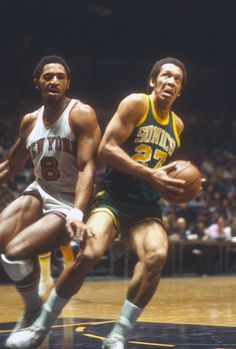 John Johnson of the Seattle Super Sonics looks to shoot over future Sonics teammate Lonnie Shelton of the New York Knicks during an NBA basketball game circa 1978 at...